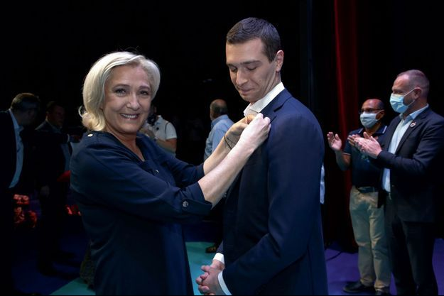 Marine Le Pen remet la flamme du RN à Jordan Bardella durant le 17e congrès du parti, à Perpignan, le 3 juillet.