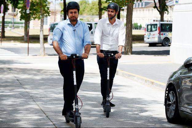 A Paris, le 31 juillet, Mounir Mahjoubi teste une trottinette électrique du service de location Bird, en compagnie du patron de l'entreprise en France, Kenneth Schlenker.