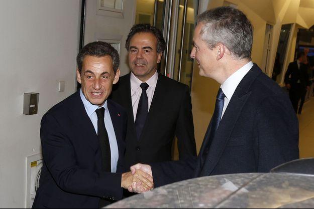 Nicolas Sarkozy serre la main de Bruno Le Maire devant le siège de l'UMP, à Paris, lundi.