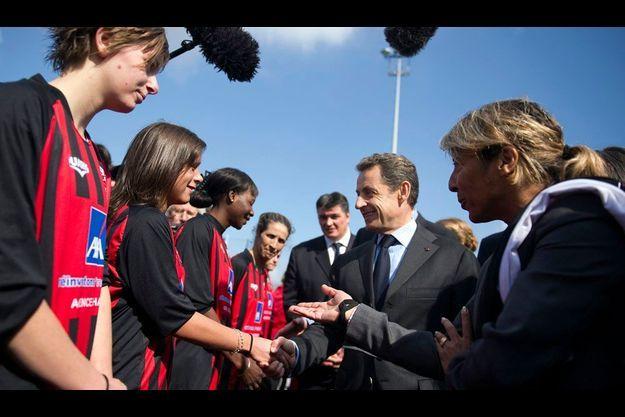 Nicolas Sarkozy salue les joueuses du FC Domont, jeudi, lors d'une visite consacrée au sport.