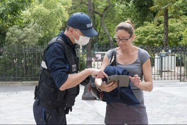 Policier municipal parisien vérifiant une attestation Covid-19.