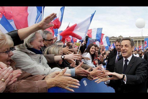 Place de la Concorde, Nicolas Sarkozy serre les mains des militants. Dans la foule, des drapeaux tricolores et un seul refrain : « On va gagner ! »