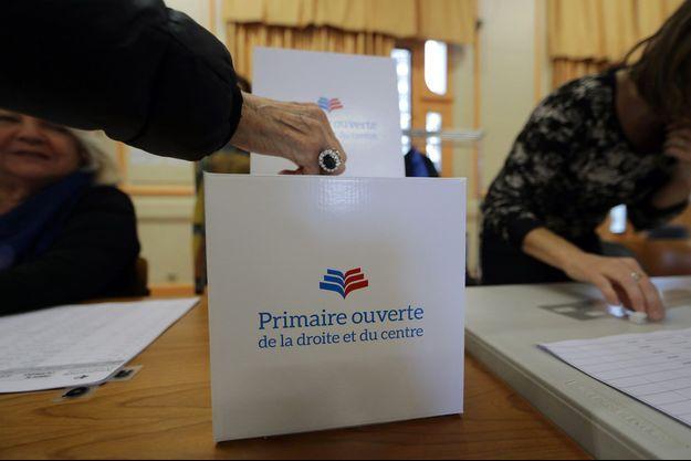 Dans un bureau de vote de Nice, une électrice s'acquitte de la contribution de 2 euros nécessaire pour pouvoir voter à la primaire de la droite.