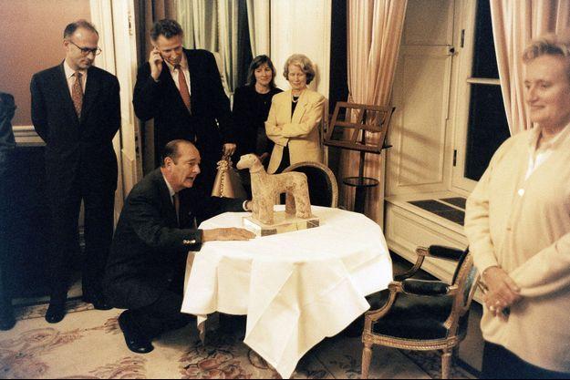 Jacques Chirac, 64 ans, heureux comme un enfant devant son cadeau, une sculpture africaine datant du XIIe siècle.