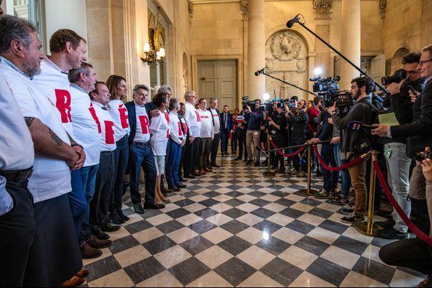 """Ici, des députés communistes arborant des t-shirts """"Référendum"""" dans les couloirs de l'Assemblée."""