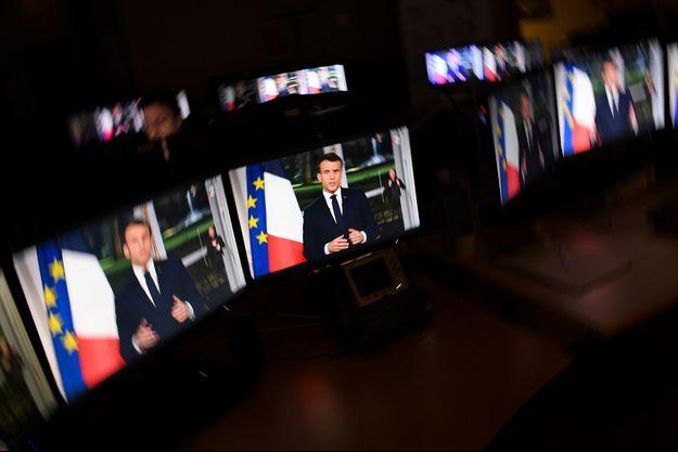 Des écrans diffusent l'allocution d'Emmanuel Macron, mardi soir à l'Elysée.