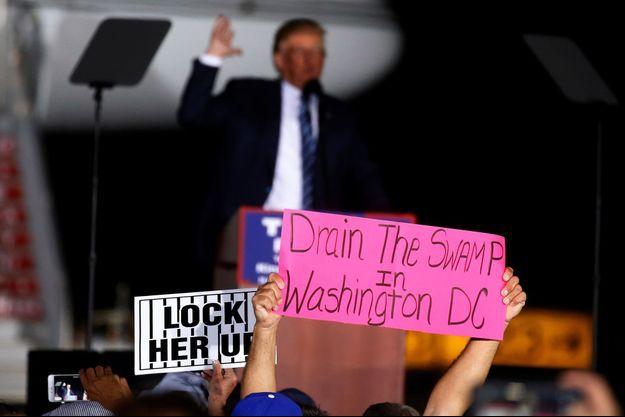 """Sur les pancartes, lors d'un meeting de Donald Trump le 27 octobre dernier en Caroline du Nord : """"Enfermez-la"""", """"Asséchez le marais de Washington D.C.""""."""