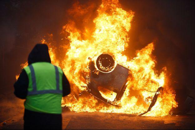 Une voiture incendiée samedi lors d'une manifestation des gilets jaunes à Paris.