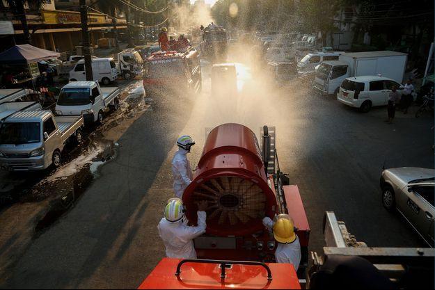 Des pompiers arrosent les rues de Rangoun, en Birmanie, avec un produit désinfectant, jeudi.