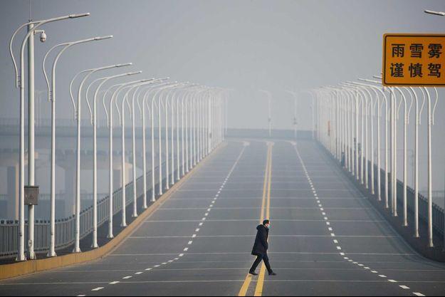 Un homme avec un masque traverse un pont, à Jiujiang, en Chine.
