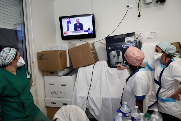 Des soignants regardant la conférence de presse de Jean Castex à Stains, le 18 mars 2021.