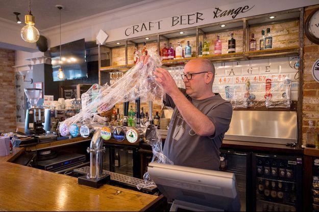 Un patron de bar prépare son établissement à rouvrir ses portes, le 12 avril prochain, à Londres.
