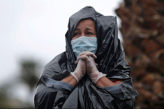Juana Gomez, 50 ans, qui n'a pas les moyens de payer le loyer et la nourriture de ses six enfants après que son mari a perdu son emploi dans la construction, se tient sous la pluie pour récupérer des aliments frais lors de la distribution de 2000 boîtes de la Banque alimentaire régionale de Los Angeles de l'épicerie, alors que la propagation de la maladie des coronavirus continue.