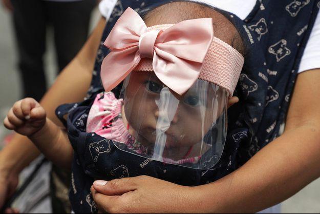 Un bébé de 6 mois masqué dans les rues de Manille, aux Philippines.
