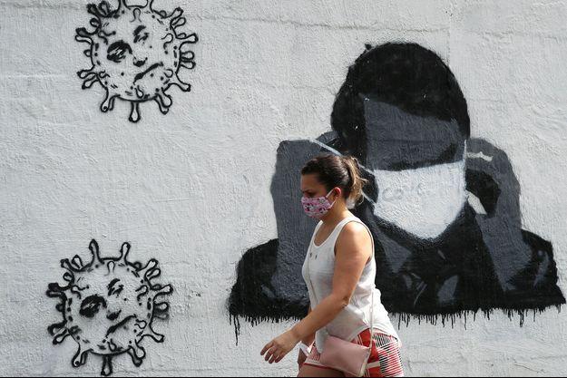 Une femme marche devant un graffiti représentant Jair Bolsonaro avec un masque de protection contre le coronavirus, à Rio de Janeiro, le 2 juillet.