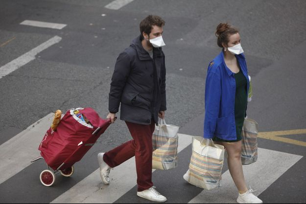 Ici des passants à Paris, lundi.