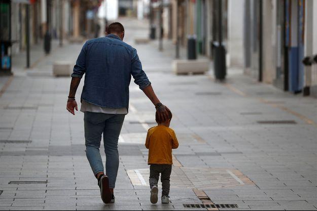 Un homme marche avec un enfant, dans les rues de Ronda, en Espagne. Image d'illustration.