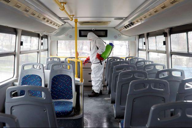 Un agent désinfecte un bus.
