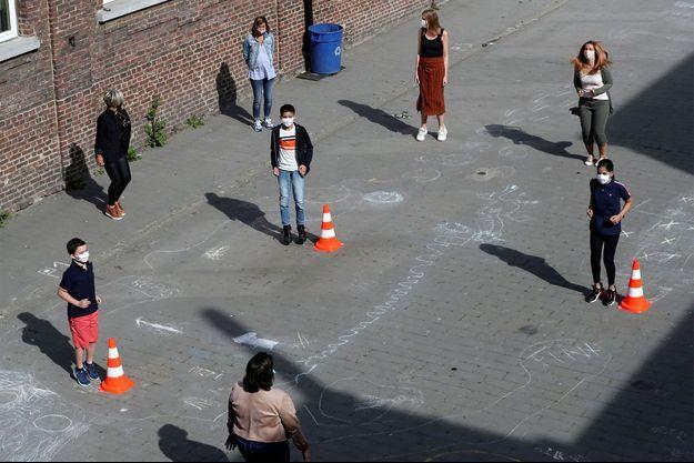 Des enfants respectent les mesures de distanciation sociale dans une école en Belgique.