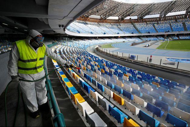 Un employé vêtu d'une combinaison de protection désinfecte les sièges du stade San Paolo avant le match retour de la demi-finale de Coppa Italia entre Naples et l'Inter Milan, qui a depuis été reportée.