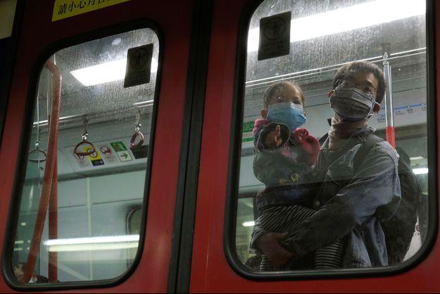 Des personnes dans le métro, à Hong-Kong.