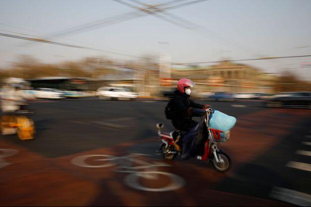 Un homme sur une moto, à Pékin, le 19 février 2020 (image d'illustration).