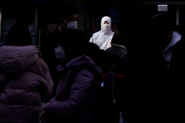 Des passagers portant des masques arrivent à la gare de Shanghai, en Chine.