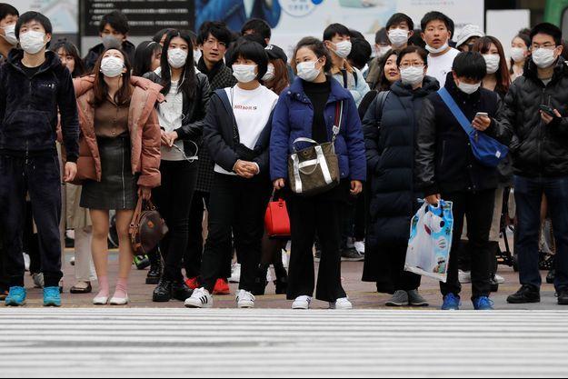 Des passants portant des masques à Tokyo, samedi 29 février.