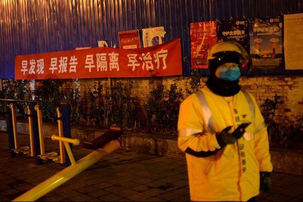 Un livreur à côté d'une affiche alertant contre le coronavirus, en Chine, le 11 février.