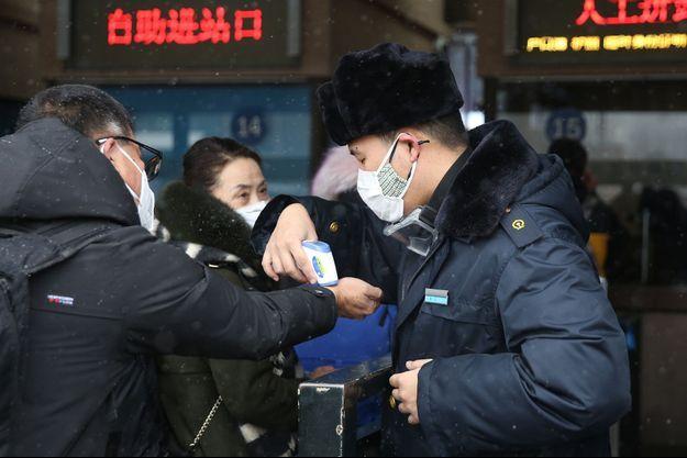 Des personnes se font contrôler leurs températures dans une station à Pékin, le 2 février 2020