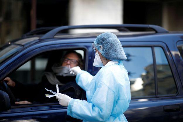 Un soignant, vêtu d'une combinaison de protection, tamponne le nez d'un conducteur sur un site de tests de dépistage de la maladie à coronavirus dans un parking en face d'un laboratoire à Neuilly-sur-Seine.