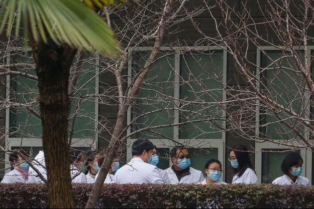 Des scientifiques et des responsables chinois en blouse de laboratoire attendent au Centre de prévention et de contrôle des épidémies animales du Hubei lors d'une visite d'une équipe de l'Organisation mondiale de la santé, à Wuhan.