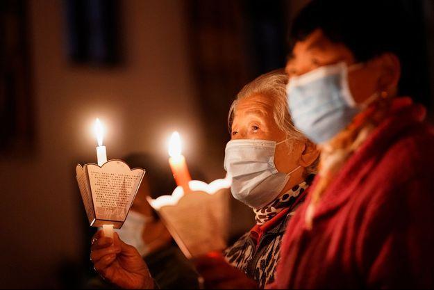 Des fidèles assistent à un service de la veillée pascale, dans une église catholique de Shanghai, en Chine.