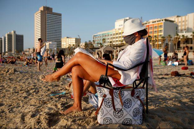 Une femme sur une plage de Tel-Aviv portant un masque, le 21 mai.