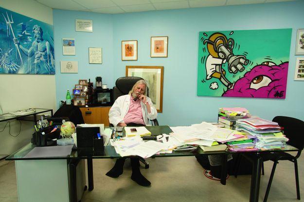 Didier Raoult dans son bureau. A dr., la toile est signée du graffeur Jace, qui a décoré l'institut.