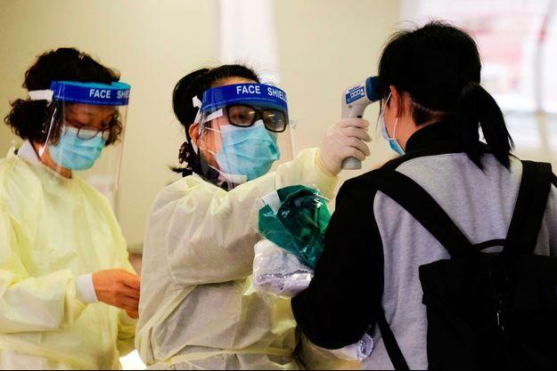 Un travailleur médical prend la température d'une femme à l'hôpital Queen Elizabeth, à Hong Kong.