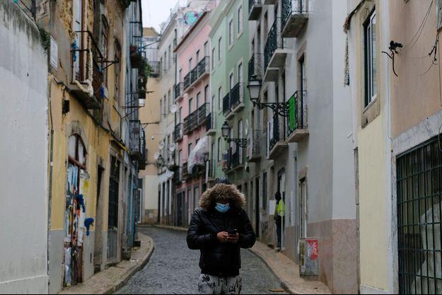 Un homme masqué marche seul dans une rue vide du Portugal.
