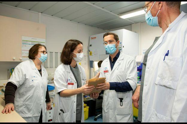 Jérémie Zerbit, le pharmacien, remet les doses de vaccin qu'il a préparées au docteur Marie Lachâtre pour une injection immédiate