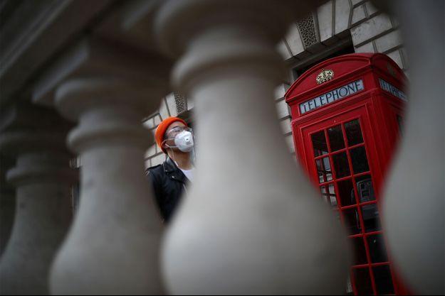 Un homme portant un masque marche à Londres.