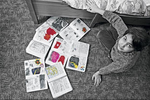 Dans la chambre, chez ses grands-parents, il expose les cahiers emplis de ses histoires incroyables.
