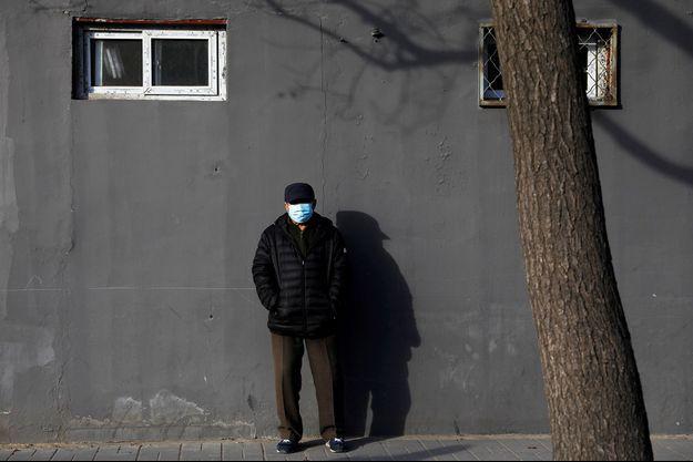 Un homme portant un masque pose dans une rue de Chine.
