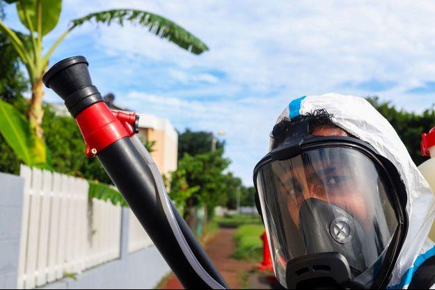 Un pompier en tenue pulvérise du produit anti-moustiques pour ralentir l'épidémie de dengue.