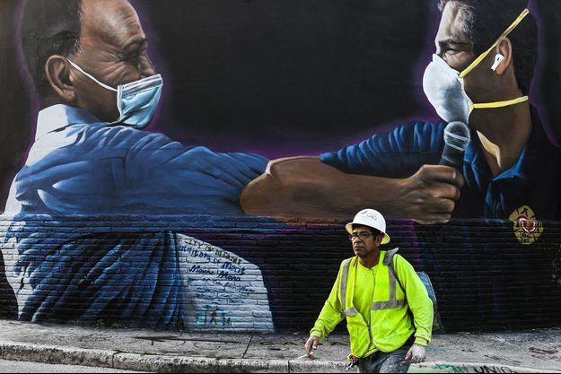 Fresque murale de Hiero Veiga représentant Moishe Mana, milliardaire promoteur immobilier à Miami et le maire de la ville Francis X. Suarez, portant des masques, à Miami, le 29 juin 2020.