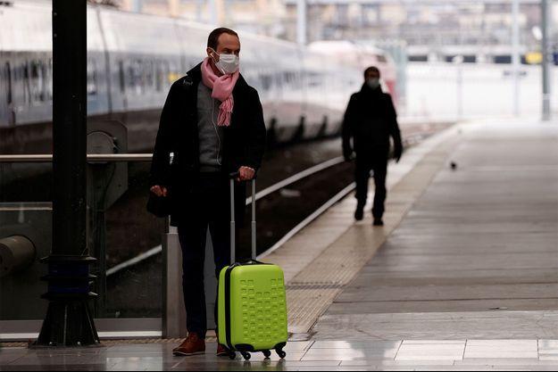 Un homme portant un masque s'apprête à prendre le train, alors que le confinement a débuté en France à 12 heures.