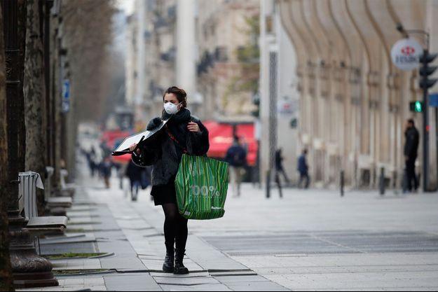 Une femme se protège du coronavirus, à Paris.