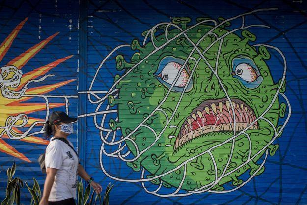 Une femme marche devant un mur représentant le virus, en Indonésie.