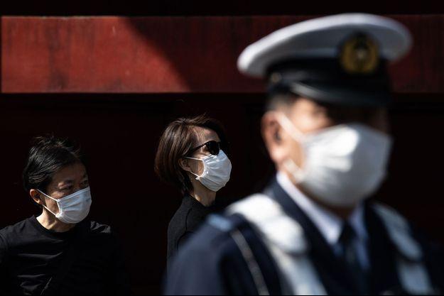 Des spectateurs observent le marathon de Tokyo en portant des masques, le 1er mars 2020