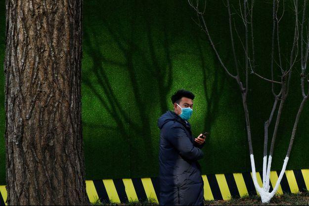 Un homme portant un masque photographié à Pékin, en Chine.