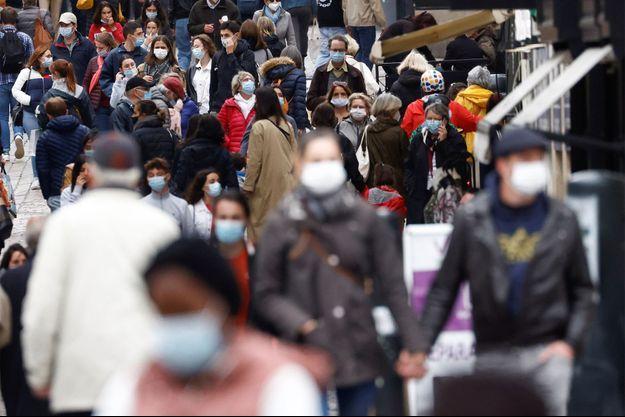 Des passants masqués dans une rue de Nantes.