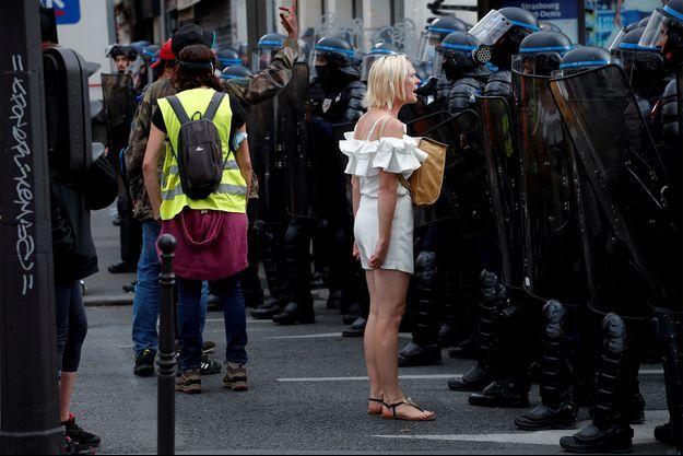 Une femme devant les forces de l'ordre lors de la manifestation samedi à Paris.